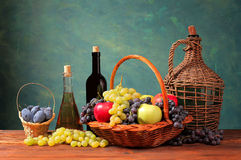 Fresh fruit in a wicker basket and bottle of wine. On the table Stock Photos