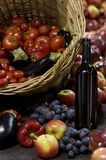 Fresh fruit and wine. A basket of fresh fruit and vegetables with some bottles of wine Royalty Free Stock Photography