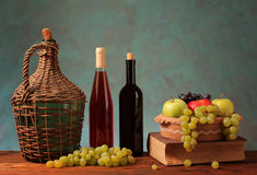 Fresh fruit and wine in glass bottles Stock Photos