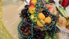 Glass bowl with fruits and beads. Fresh fruit wrapped in beads with garlands to decorate the wedding table stock footage