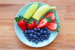 Fresh fruites plate with bananas, strawberry, blueberry stock photography
