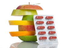 Fresh Fruits. A stack of different fruits and some capsules - isolated on a white backgorund Royalty Free Stock Images