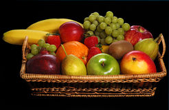 Fresh fruits. Assortment of fresh fruits in basket with black background stock photography