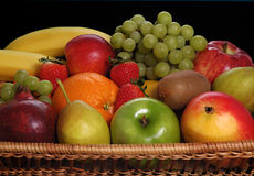 Fresh fruits. Assortment of fresh fruits in basket with black background stock images