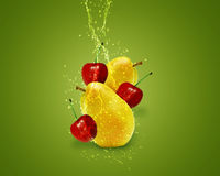 Fresh Fruits. Fresh Pear, cherry with water splashes on green background Royalty Free Stock Image
