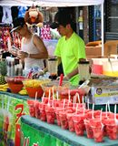 Fresh Fruits. Young Chinese street vendors selling fresh fruits juice during June 2012, Maspeth Stret Fair Royalty Free Stock Photos