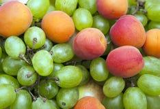 Fresh fruits background. Fresh fruits apricot and grape background royalty free stock image