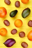 Fresh fruits background, top view. Variety of fresh organic fruits including oranges, kiwi fruits, mango, grapefruits and avocado on yellow wooden background Royalty Free Stock Images