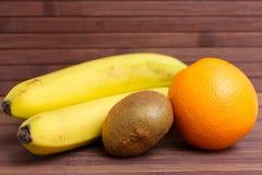 Fresh fruits banana, kiwi, orange isolated on wooden background. Healthy food. A mix of fresh fruit. Group of citrus fruits. Stock Photo