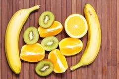 Fresh fruits banana, kiwi, orange isolated on wooden background. Healthy food. A mix of fresh fruit. Group of citrus fruits. Stock Photos