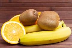 Fresh fruits banana, kiwi, orange isolated on wooden background. Healthy food. A mix of fresh fruit. Group of citrus fruits. Vegetarian raw fruit. Nutrition Stock Photos