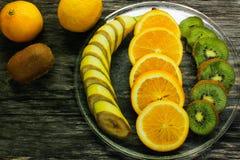 Fresh fruits banana, kiwi, orange on wooden background. Healthy food. A mix of fresh fruit. Group of citrus fruits. Vegetarian raw Royalty Free Stock Images