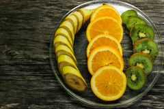 Fresh fruits banana, kiwi, orange on wooden background. Healthy food. A mix of fresh fruit. Group of citrus fruits. Vegetarian raw Royalty Free Stock Photo