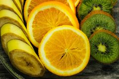 Fresh fruits banana, kiwi, orange on wooden background. Healthy food. A mix of fresh fruit. Group of citrus fruits. Vegetarian raw Royalty Free Stock Photos