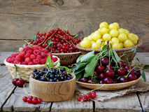 Fresh fruits and berries in the basket on wooden background. Raspberries, cherries, red and black currant, yellow plum, white mulberry royalty free stock images