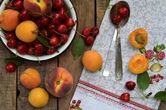 Fresh fruits and berries on wooden background. Ripe sweet cherry and apricot in bowl on the kitchen table. Stock Image