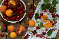 Fresh fruits and berries on wooden background. Ripe sweet cherry, currants, peach and apricot, mulberry on the kitchen table. Stock Photography