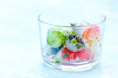 Fresh fruits and berry frozen in ice cubes on blue background. F Royalty Free Stock Image