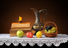 Fresh fruits, books and metal carafe Royalty Free Stock Images