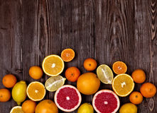 Fresh fruits citruses on a dark wooden background. Raw and vegetarian eating frame. Stock Photography