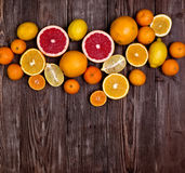 Fresh fruits citruses on a dark wooden background. Raw and vegetarian eating frame. Stock Photos