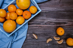 Fresh fruits citruses on a dark wooden background. Raw and vegetarian eating frame. Sliced tangerines, oranges, grapefruits, blue Royalty Free Stock Images