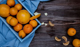 Fresh fruits citruses on a dark wooden background. Raw and vegetarian eating frame. Sliced tangerines, oranges, grapefruits, blue Stock Image