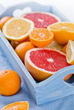 Fresh fruits citruses on a white wooden background. Raw and vegetarian eating frame. Sliced tangerines, oranges, grapefruits, blue Royalty Free Stock Photo