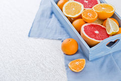Fresh fruits citruses on a white wooden background. Raw and vegetarian eating frame. Sliced tangerines, oranges, grapefruits, blue Royalty Free Stock Images