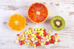 Fresh fruits and colorful medical pills, choice between healthy nutrition and medical supplements. Fresh natural fruits and medical pills, tablets and capsules Royalty Free Stock Images