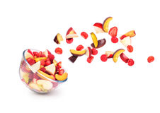 Fresh fruits coming out from a bowl. Isolated on a white background stock photography