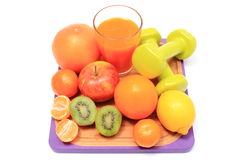 Fresh fruits, dumbbells and glass of juice Royalty Free Stock Images