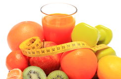 Fresh fruits, dumbbells, tape measure and glass of juice Stock Photos