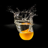 Fresh fruits falling in water with splash on black background Royalty Free Stock Photography
