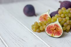 Fresh fruits - figs and grapes over white wooden background. Royalty Free Stock Photos