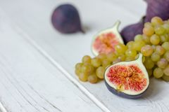 Fresh fruits - figs and grapes over white wooden background. Stock Photography