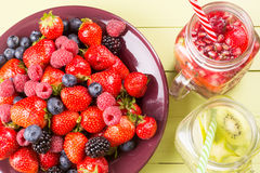 Fresh fruits flavored water in jars and mixed soft fruits. Fresh fruits flavored water healthy detox drinks in jars and plate of soft fruits - top view stock images