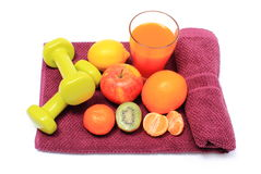 Fresh fruits, glass of juice and dumbbells on purple towel Royalty Free Stock Photos