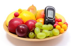 Fresh fruits and glucose meter on wooden plate Royalty Free Stock Photos