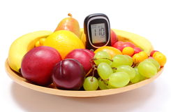 Fresh fruits and glucose meter on wooden plate Royalty Free Stock Photography