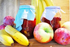 Fresh fruits and jars on wooden background Stock Photography