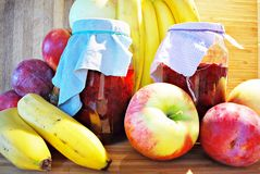 Fresh fruits and jars on wooden background Stock Photos