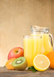 Fresh fruits juice in glass and slices on wood Stock Image