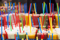 Fresh fruits juices and colorful drinking straw Stock Photos