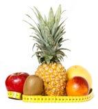 Fresh fruits with measuring tape isolated. Fresh fruits (apple, pineapple, kiwi, orange, grapefruit) and measuring tape isolated on white Stock Images