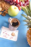 Love you note near coffee and fruits. Fresh fruits and nuts on a blue wooden table, cup of Arabic coffee and a paper note with love you message and heart shaped Stock Photography