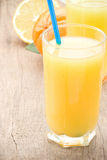 Fresh fruits orange juice in glass on wood board Royalty Free Stock Photos