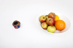 Fresh fruits in plate with cupcake against white background Stock Photography