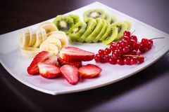 Fresh fruits on a plate. Strawberries, banana slices, berries with kiwi on a plate stock images