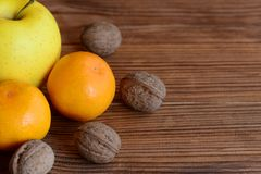 Fresh ripe mandarin, apple, walnuts on a wooden table. Organic sources of vitamins and minerals. Healthy nutrition Royalty Free Stock Images